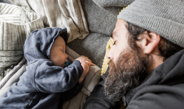 BABYBJÖRN Magazine – Baby sleep habits: Dad and baby snuggle together in the camper van.